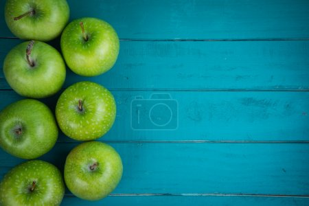 Farm fresh organic green apples on wooden retro blue table  with