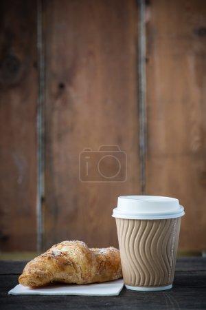 Photo pour Emporter le café et le croissant frais sur le fond en bois - image libre de droit