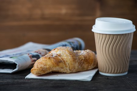 Take away coffee and fresh croissant and newspaper