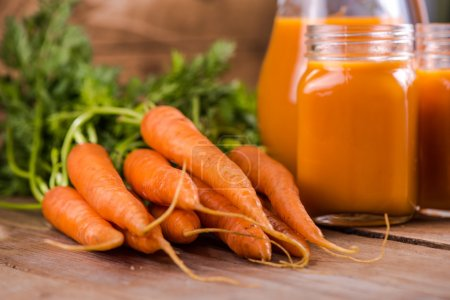 Photo for Carrot juice in mason jar on wooden background, whole carrots - Royalty Free Image