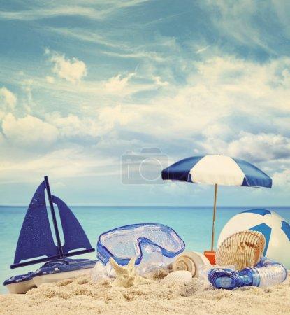 Jouets de plage sur la plage de sable fin avec une mer bleue à l'arrière-plan