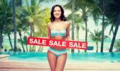 happy young woman in swimsuit with red sale sign