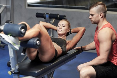 woman with personal trainer doing sit ups in gym