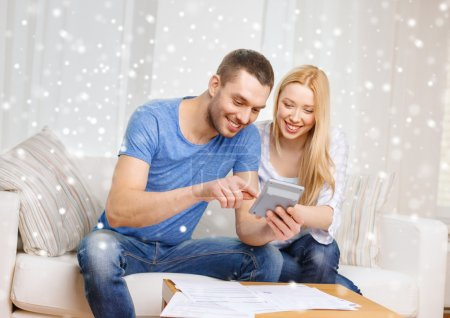 happy couple with papers and calculator at home