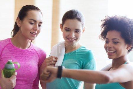 happy women showing time on wrist watch in gym