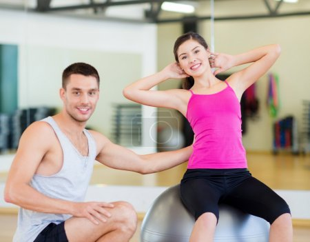 male trainer with woman doing crunches on the ball