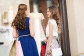 """Постер, картина, фотообои """"happy women with shopping bags at shop window"""""""
