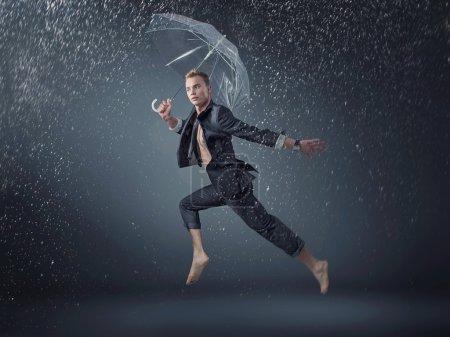 Photo pour Beau mec sauter et danser sous la pluie - image libre de droit