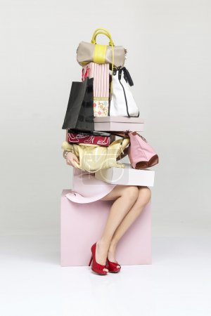Conceptual picture of a woman holding plenty of handbags