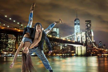 Photo pour Jeune couple hip hop dansant sur fond urbain - image libre de droit