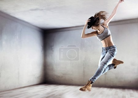 Athletic dancer jumping on a concrete wall background