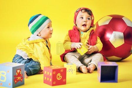 Cute siblings playing toy bricks