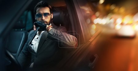 Outdoor portrait of fashion man driving a car