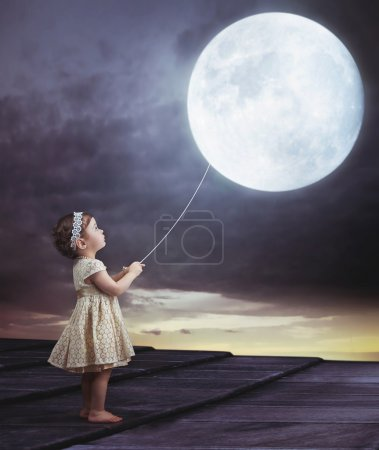 Photo for Fairy portait of a little cute girl with a moony balloon - Royalty Free Image
