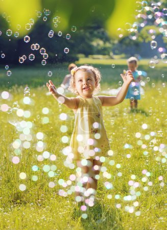 Photo pour Portrait de deux petites filles jouant ensemble les bulles de savon - image libre de droit