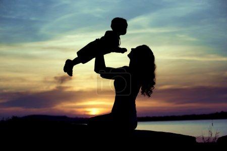 Femme soulevant son enfant