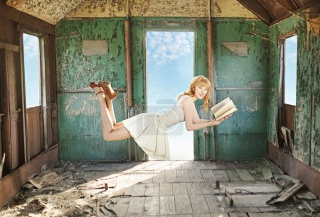 Glad levitating redhead with the book
