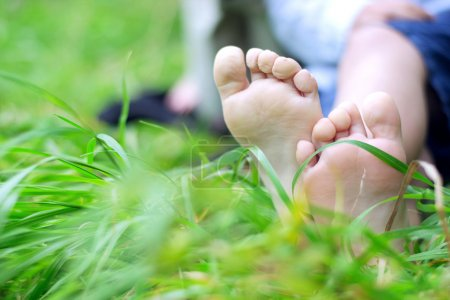 Photo pour Pieds de petit garçon sur de l'herbe fraîche - image libre de droit