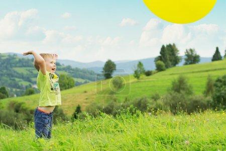 Photo pour Souriant garçon rebondissant un ballon - image libre de droit