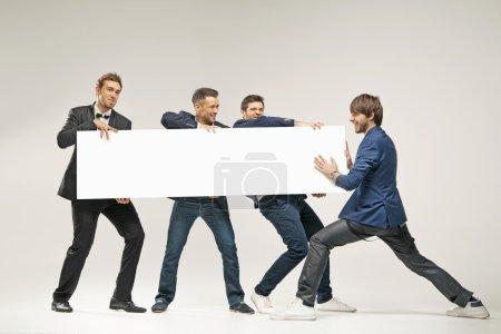 Photo pour Groupe de beaux hommes poussant une planche - image libre de droit