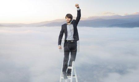 Photo pour Beau mec sur l'échelle au-dessus des nuages - image libre de droit