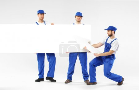 Three handsome builders holding signs