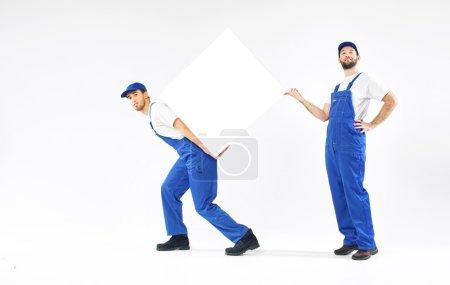 Photo pour Deux jeunes bâtisseurs tenant un tableau blanc - image libre de droit