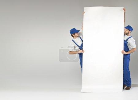 Foto de Dos hermosos constructores sosteniendo una tabla vacía - Imagen libre de derechos