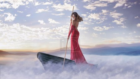 Photo for Alone smart lady paddling in the clouds - Royalty Free Image