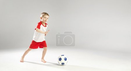 Little talented boy playing football