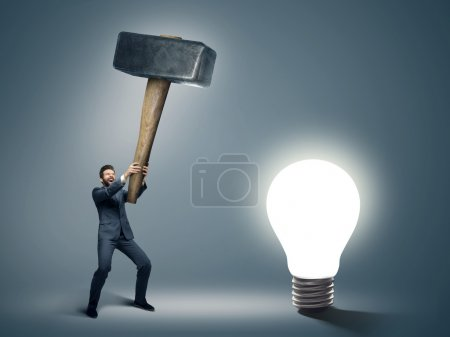 Conceptual image of a businessman holding huge hammer