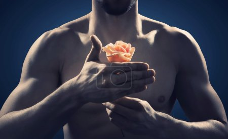 Strong and fit man holding a rose