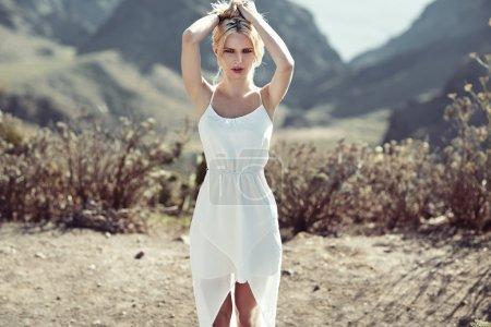 Sensual blond woman walking on the desert