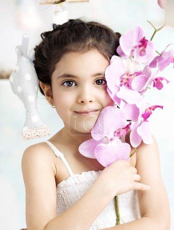 Little brunette girl holding a flower