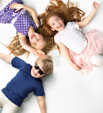 Portrait of siblings lying on a white background