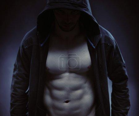 Hooded sportsman hidiing himself in the dark