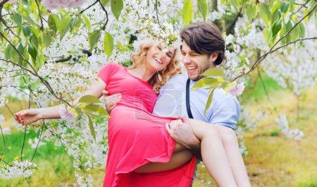 Joyful couple in the fragrant orchard