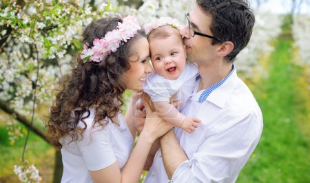 Cheerful parents kissing their beloved child