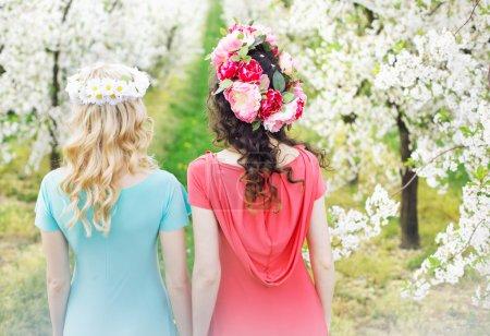 Two beautiful women walking along the flower alley