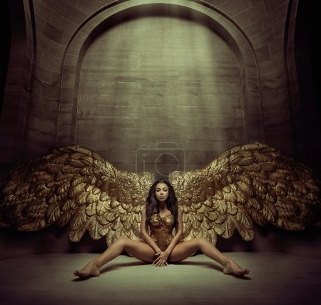Alluring young angel in the dark hall
