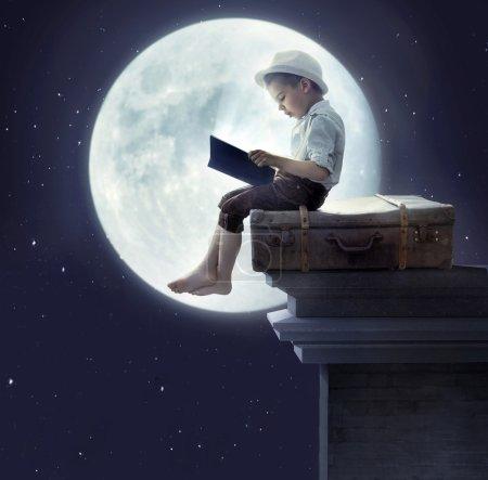 Portrait of a little boy reading a book