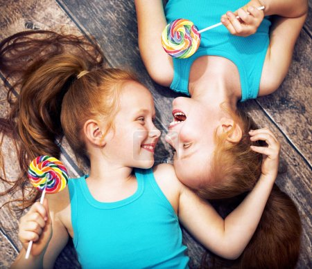 Fine portrait of a twin sisters holding lollipops