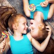 Fine portrait of a twin sisters holding colorful  ...
