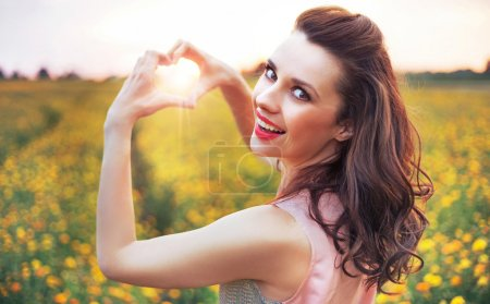 Beautiful woman making a heart sign