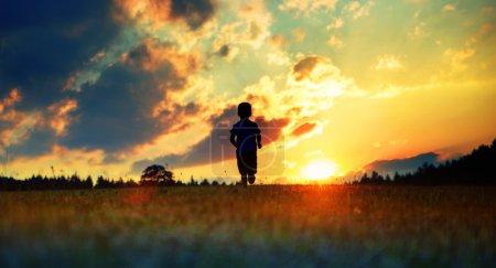 Cheerful boy running towards the sunset