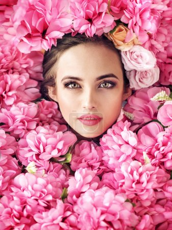 Photo for Beautiful female face among rose flowers - Royalty Free Image