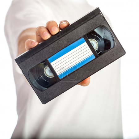 Video tape cassete (VHS) with blue label hold by m...