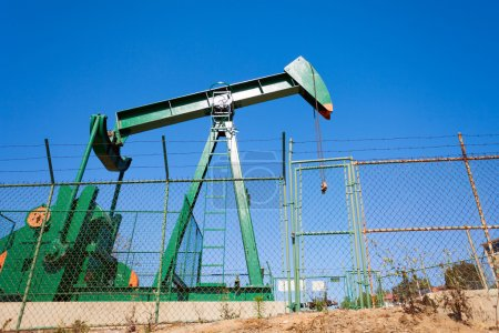 Green out of order oil-derrick surrounded by the c...