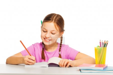 Photo for Pretty diligent schoolgirl in pink tee writing with orange pencil at school - Royalty Free Image
