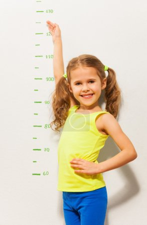 Photo pour Joyeux sourire petite fille mesurer la hauteur avec la main sur l'échelle dessinée sur le mur - image libre de droit